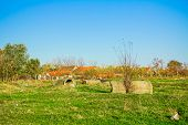 picture of suburban city  - Concrete pipes scattered on green meadow with city nearby - JPG