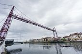 stock photo of suspension  - Closeup Wide view of the Bizkaia suspension bridge against cloudy sky and trainera in Portugalete - JPG
