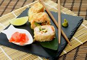 picture of avocado  - Hot Tempura Roll with Salmon and Avocado Served with Lime and Ginger on Black Plate closeup on Straw Mat background - JPG