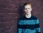 stock photo of redhead  - Young redhead man in a sweater and jeans standing next to the red brick wall - JPG