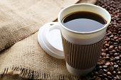 stock photo of sackcloth  - Paper cup of coffee with beans on sackcloth close up - JPG