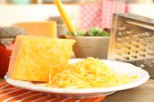 pic of grating  - Grated cheese on wooden table - JPG