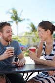 stock photo of late 20s  - Cafe couple having fun drinking coffee talking smiling and laughing on date in summer - JPG