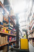 foto of forklift driver  - Focused driver operating forklift machine in warehouse - JPG