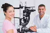 foto of slit  - Portrait of happy optician and female patient with slit lamp in clinic - JPG
