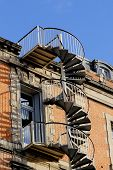 picture of spiral staircase  - External metal spiral staircase fire escape in sunlight - JPG