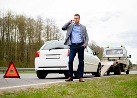 pic of towing  - Man calling while tow truck picking up his broken car  - JPG