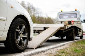 image of trucks  - Loading broken car on a tow truck on a roadside  - JPG