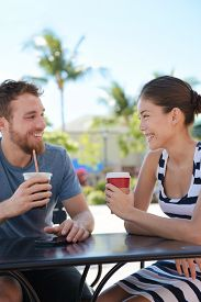 picture of late 20s  - Cafe couple having fun drinking coffee talking smiling and laughing on date in summer - JPG