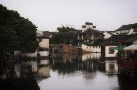 stock photo of tong  - White asian designed buildings reflecting off of the water canals of Tongli Town in Jiangsu Province China - JPG