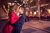 Young affectionate couple kissing tenderly on Christmas street  poster