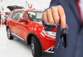 Car dealer with a key. Auto dealership and rental concept background. poster