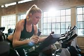 Woman Working Out On Exercise Bike At The Gym poster