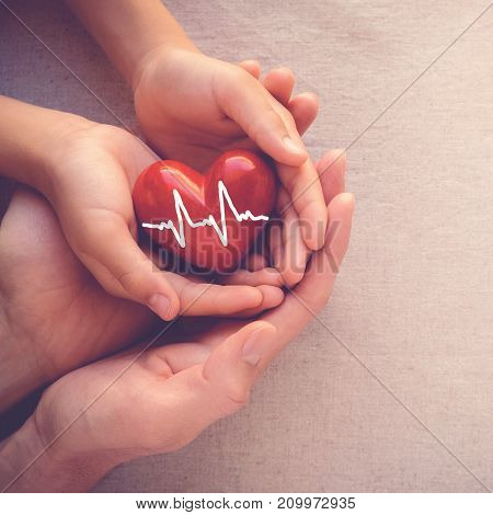 poster of adult and child hands holiding red heart with cardiogram health care love and family concept