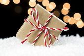 Small Gift Box Wrapped In Brown Paper And Twine Wedged In White Snow. Black Background With Soft Hol poster
