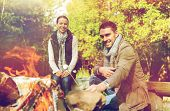 travel, tourism and hike concept - happy couple roasting marshmallow over campfire at camp in woods poster