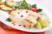 stock photo of halibut  - Grilled halibut with capers and pepper sauce served with lemon lime tomatoes and green peas - JPG