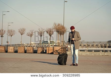 poster of Moving To New City Alone. Man Bearded Hipster Travel With Luggage Bag On Wheels. Traveler With Suitc