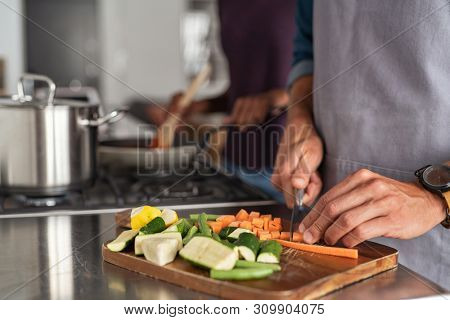 poster of Closeup of hands slicing carrots on chopping board. Closeup of hands cutting vegetables in kitchen n