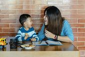 Asian Single Mom With Son Are Drawing And Eating Cookie Together When Living In Loft House For Self  poster