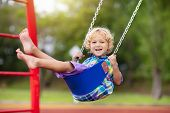 Child On Playground. Swing Kids Play Outdoor. poster