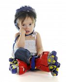 An adorable preschooler weepy because her plastic roller blades made her fall.  On a white backgroun
