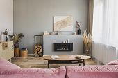 Stylish Living Room Interior With Pastel Pink Sofa, Wooden Coffee Table And Eco Fireplace poster