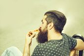 Handsome Sexy Bearded Young Man Hipster With Long Beard And Mustache On Serious Hairy Face Eating Pi poster