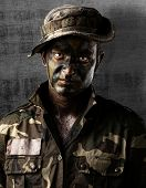 portrait of a young soldier face painted with jungle camouflage against a grunge wall