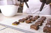 Production Of Chocolate Candies. Hands Close-up. Baker Dips Candies In Melted Chocolate And Put It O poster