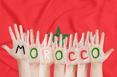 Inscription Morocco On The Childrens Hands Against The Background Of A Waving Flag Of The Morocco poster