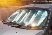 Protective Reflective Surface Under The Windshield Of The Passenger Car Parked On A Hot Day, Heated  poster