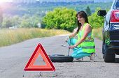 Girl Despair With Spare Wheel Replacement. Punched Wheel On The Road While Driving. Girl L In Reflec poster