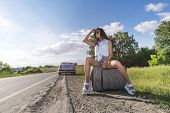 Young Woman Hitch-hiking On A Road With Luggage Bag At Fields. Girl Is Sitting On Baggage And Waitin poster