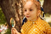 Closeup Portrait Of Curious Little Girl Playing With Magnifying Glass, Exploring The Nature Outdoor. poster