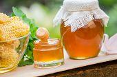 Honey Pot, Dipper, Jar Of Fresh Honey, Honeycomb On A Wooden Table Outdoors. Honey With Honey Dipper poster