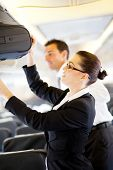 stock photo of flight attendant  - friendly flight attendant helping passenger with carry on luggage - JPG
