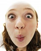 Close-up, fish-eye view of a preteen making a wide-eyed kissing face.  On a white background.