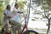 picture of tandem bicycle  - Older couple riding tandem bicycle - JPG