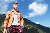 young casual man posing outdoor in the mountains, looking down into the camera while holding a hand
