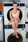 Portrait of happy young woman sitting in washing machine