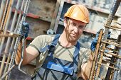 foto of concrete pouring  - Portrait of builder worker concreter with metal rods bars at framework reinforcement for concrete pouring in construction site - JPG
