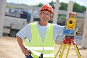 Portrait of builder worker with theodolite transit equipment at construction site outdoors during su