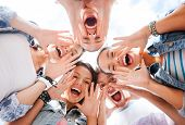 summer holidays and teenage concept - group of teenagers looking down and screaming