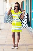 happy african woman with shopping bags in mall