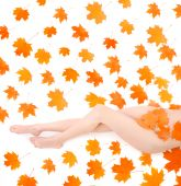 picture of woman legs  - Long beautiful legs of nudity woman covering by maple leafs over white - JPG