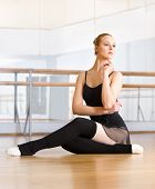 Ballet dancer does exercises sitting on the floor in the classroom with barre and mirrors