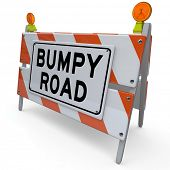 The words Bumpy Road on a barrier or blockade as a warning sign that trouble, problems, issues or ob