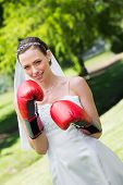 foto of boxing day  - Portrait of happy young bride with red boxing gloves in park - JPG