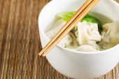 stock photo of wanton  - Extreme close up horizontal photo of freshly made wonton with chopsticks on top of white bowl